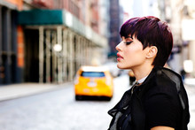 Profile Portrait Of A Stylish Young Girl With Short Purple Hair And A Yellow Taxi In The Background
