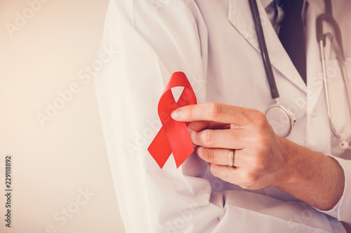 Photo Doctor hand holding red ribbon, world AIDS day