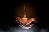 Hands holding candle over dark background