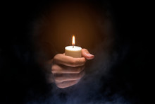 Hands Holding Candle Over Dark...