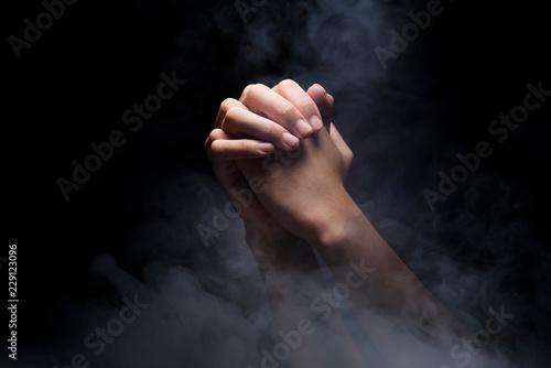 Praying hands over dark background Fototapeta