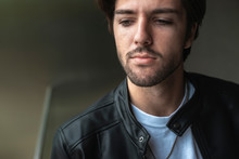 Close Up Portrait Of Handsome Confident Young Man Looking Down Wearing Black Leather Jacket