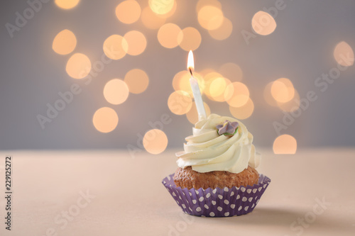 Photo  Delicious birthday cupcake with burning candle on table against blurred lights