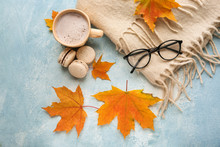 Composition With Cup Of Aromatic Coffee, Warm Plaid And Autumn Leaves On Color Background