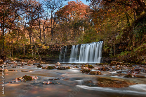 Foto op Plexiglas Panoramafoto s Waterfall Ddwli Uchaf near pontneddfechan in the brecon beacons national park, Wales. It is autumn, and golden leaves are all around. Long shutter speed for a smooth effect on the water