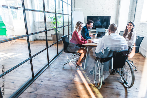 Obraz young disabled businessman in wheelchair working with colleagues in office - fototapety do salonu