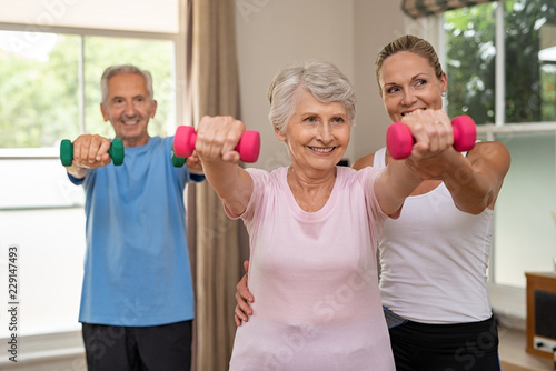 Senior couple exercising using dumbbells