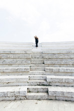 Woman In A Black Dress And A Hat Walking The Stairs Of An Amphitheater.