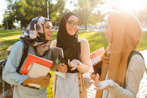 Happy friends muslim sisters women walking outdoors holding books Wallpaper Mural