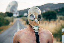 Naked Man With Tear Gas Mask On A Road.