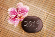 2019 written on a black pebble with pink orchid, zen greeting card