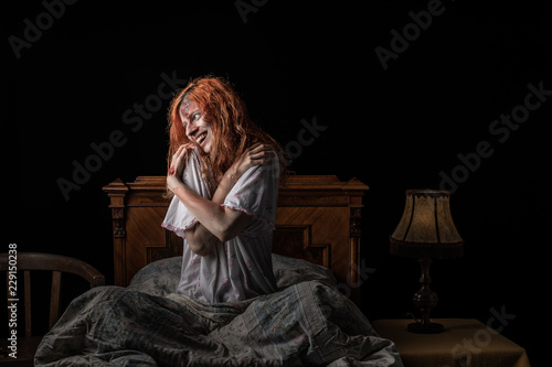 Fotografia  Scary woman possessed by devil in the bed. Exorcism of priest.