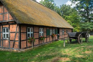 Fototapeta na wymiar Fachwerk-Reetdachhaus im Heidedorf Wilsede (Ortsteil von Bispringen) im Heidekreis im Naturschutzgebiet Lüneburger Heide in Niedersachsen in Deutschland.