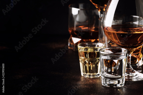 Poster de jardin Alcool Set of strong alcoholic drinks in glasses and shot glass in assortent: vodka, rum, cognac, tequila, brandy and whiskey. Dark vintage background, selective focus