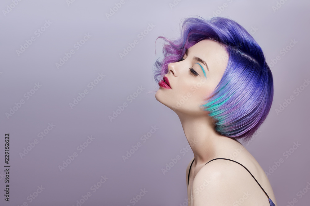 Fototapeta Portrait of a woman with bright colored flying hair, all shades of purple. Hair coloring, beautiful lips and makeup. Hair fluttering in the wind. Sexy girl with short  hair. Professional coloring