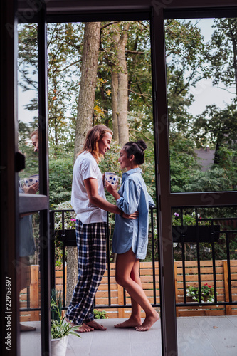 So romantic. Positive nice couple drinking tea while standing together on the balcony