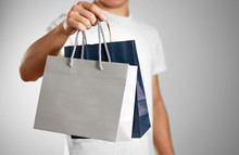 Man Holding A Blue And Grey Gift Bags. Close Up. Isolated Background