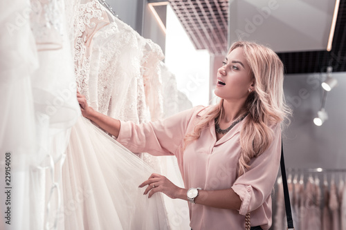 Its beautiful. Pleasant nice woman expressing her emotions while looking at the beautiful wedding dress