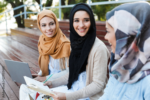 Friends muslim sisters women sitting outdoors using laptop computers Canvas