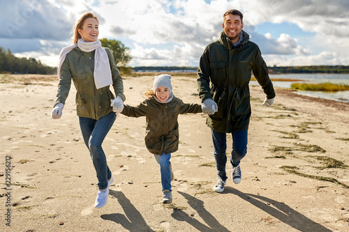 family, leisure and people concept - happy mother, father and little daughter running along autumn beach