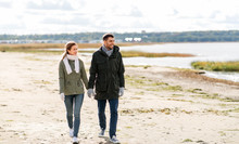 Love, Relationship And People Concept - Smiling Couple Walking Along Autumn Beach And Holding Hands