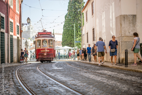 Red tram on historic streets of Lisbon, capital city of Portugal