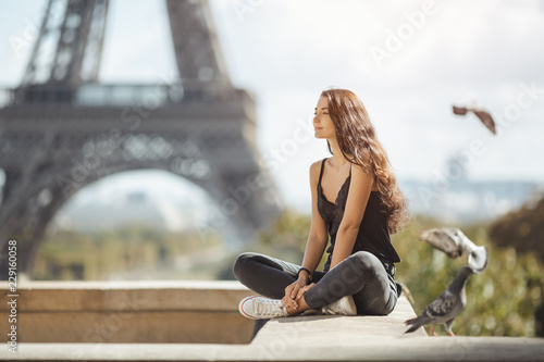 Happy travel woman near the Eiffel tower, Paris. Travel tourist girl on vacation resting happy outdoors. Pigeons symbol of love flying around fliynig Attractive young romantic woman sitting against