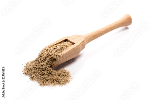 Fototapeta Close-up of pile of ground cardamom spice in a wooden spoon on white background obraz