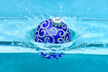 Holidays And Vacation Concept. Festive Decoration For Christmas Tree, Blue Ball Dropped Into Water With Splashes, Blue Background. Christmas Decoration Or Toy For Christmas Tree Swim In Pool