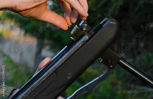 the hunter charges the air rifle with a projectile