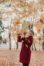 Cheerful Woman Throwing Leaves Up