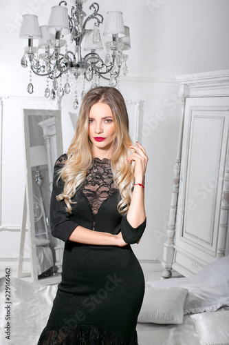 Beautiful smiling blonde in a black dress in a room with a classic interior.