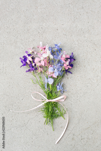 Bouquet of delicate wild flowers tied with ribbon on grey stone background with copy space. Vertical greeting card in pastel colors.