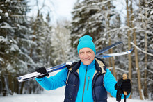 Happy Senior Sportsman With Skis Looking At You While Standing In Forest On Winter Day