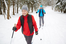 Happy Mature Woman In Sportswear Skiing With Her Husband In Winter Forest
