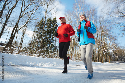Papiers peints Glisse hiver Happy active seniors in sportswear jogging down winter road in natural environment