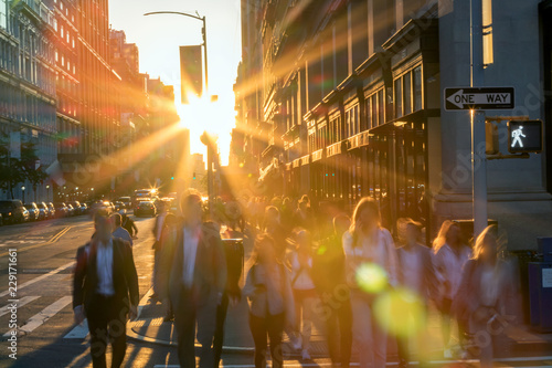 Recess Fitting New York Crowd of blurred people crossing a busy intersection on 5 th Avenue in New York City with the bright light of sunset in the background
