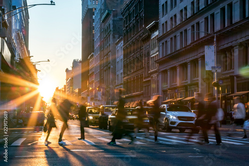 Photo sur Toile New York Rays of sunlight shine on the busy people walking across an intersection in Midtown Manhattan in New York City