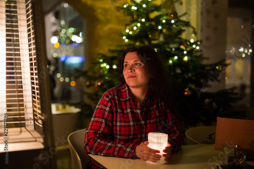 Fototapety, obrazy: Holidays and people concept - Beautiful woman in cafe near Christmas tree background