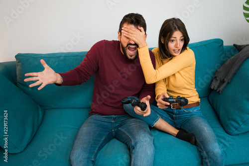 Fotografie, Obraz  Beautiful attractive couple playing games together sitting on the couch and laughing, losing the game