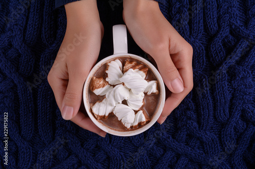 Feminine hands holding hot chocolate with marshmallow candies on blue knitted plaid. Top view. Copy space