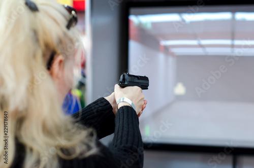 Fotomural  Woman shooting in virtual shooting gallery