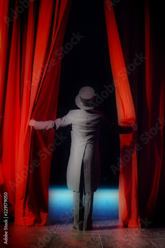 Fotografia  Actor in a tuxedo and hat looks behind the theater curtain