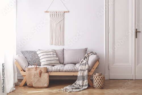 Fotografía  Handmade wicker bags on herringbone parquet floor of a warm living room interior