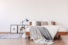 Comfortable King Size Bed With Pillows And Blankets In Bright Bedroom Interior With Rustic Carpet On The Floor, Real Photo With Copy Space