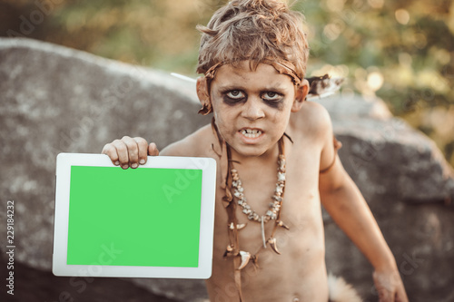 Photo  Caveman, manly boy holding tablet PC with green screen