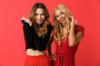 Leinwanddruck Bild - Happy young friends women standing isolated over red background.