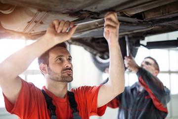 Fototapeta Car mechanics working at automotive service center