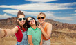 travel, tourism and vacation concept - group of happy female smiling friends in sunglasses taking selfie over grand canyon national park background