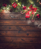 Fototapeta Tulipany - Christmas background with ornaments and gift boxes on the old wooden board